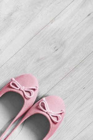 flat shoes: Pink textile flat shoes on white wooden floor Stock Photo