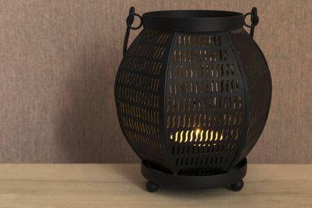 Black metal lamp with burning tea light closeup