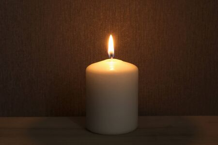flame background: Single burning candle against the wall closeup