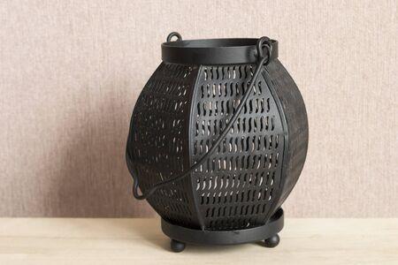 tea lamp: Black metal tea light lamp on a table Stock Photo