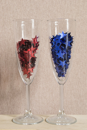 star shaped: Champagne glasses full of red and blue star shaped confetti