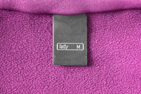 fleece: Black clothes label on pink fleece as a background Stock Photo