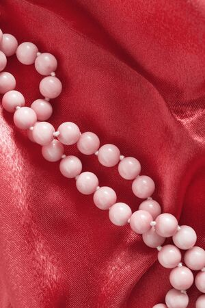 draped cloth: Strings of pink coral beads on red silk