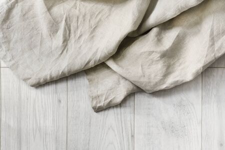 draped cloth: Beige folded linen on white wooden floor as a background Stock Photo