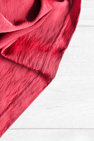 draped: Red draped silk on white wooden background closeup