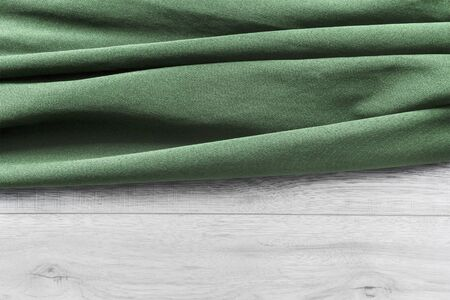 draped cloth: Folded green cloth on white wooden planks as a background Stock Photo