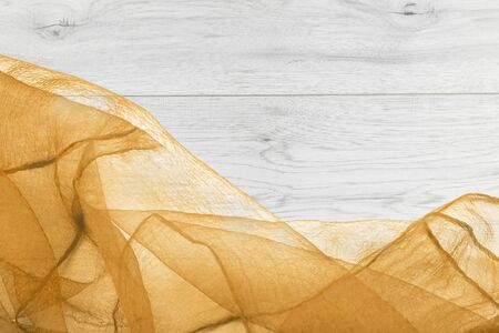 draped cloth: Crumpled yellow transparent chiffon on gray wooden background
