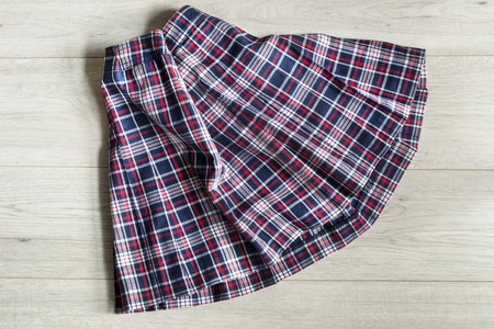 木製の背景のクローズ アップに制服のタータン チェックのスカートを折り 写真素材