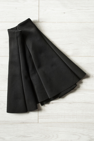 basics: Black basics mini skirt folded on wooden background