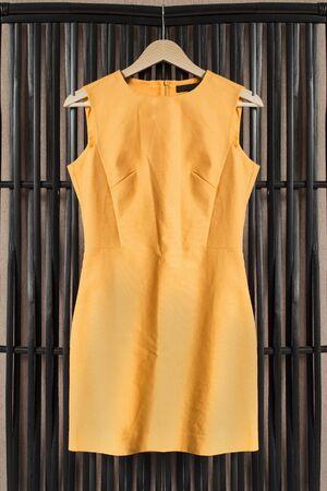 sleeveless dress: Yellow sleeveless dress on clothes rack hanging on wooden screen