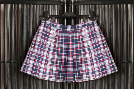 pleated: Tartan pleated skirt on clothes rack hanging on black bamboo screen