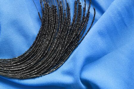 draped cloth: Black glass beads on blue draped silk as a background