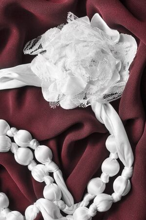 draped cloth: White silk decorative accessories on draped red cloth as a background