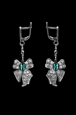 topaz: Topaz and crystals earrings in the shape of a bow isolated over black