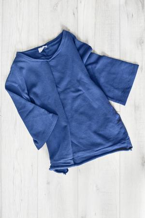 sudadera: Blue crumpled sweatshirt on white wooden background