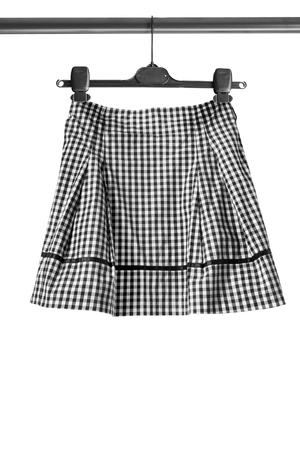 checkered skirt: Black and white checkered skirt on clothes rack isolated over white