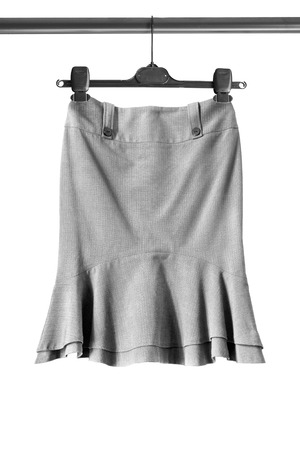 formal dressing: Gray elegant skirt on clothes rack isolated over white