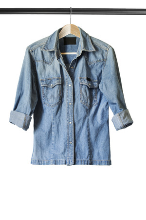 Blue casual denim shirt on clothes rack isolated over white