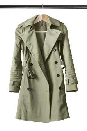 白で分離された服のラックにカーキ コットン トレンチ コート 写真素材