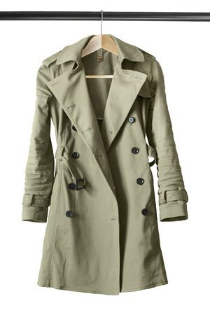 Khaki cotton trench coat on clothes rack isolated over white Archivio Fotografico