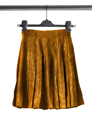 pleated: Pleated golden shiny skirt on clothes rack isolated over white