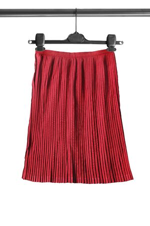pleated: Red pleated skirt on clothes rack isolated over white Stock Photo