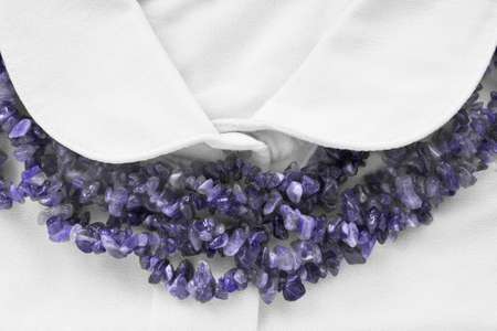 formal dressing: Strings of amethyst beads on white blouse closeup