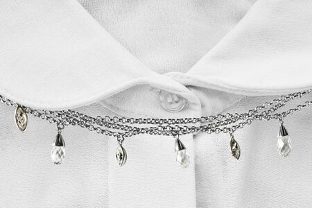 neckband: Chain necklace on white blouse closeup as a background Stock Photo