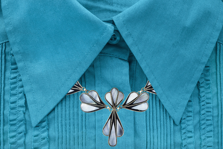 neckband: Nacre necklace on blue blouse closeup as a background