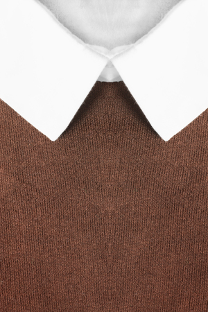 neckband: White shirt collar on brown pullover as a background Stock Photo