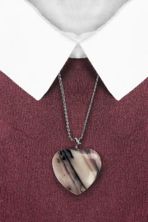 formal dressing: Agate heart pendant on red pullover with white collar closeup Stock Photo