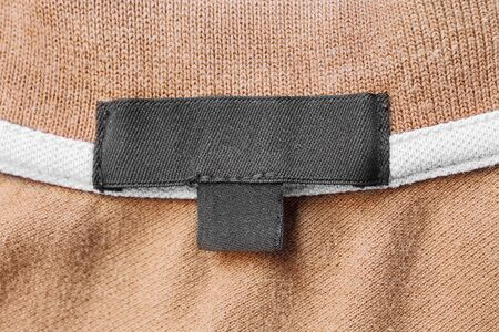 label tag: Blank black clothes label on beige cloth as a background Stock Photo