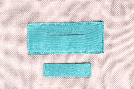 docket: Blank cyan clothes label on pink cloth as a background