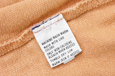 docket: Washing instructions label on yellow cloth as a background