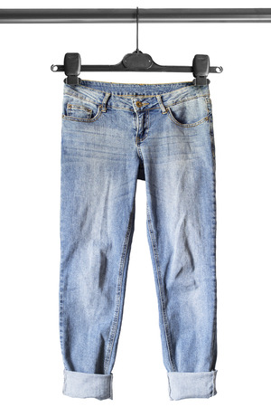 Blue casual jeans on clothes rack isolated over white Archivio Fotografico