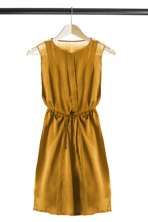 chiffon: Yellow chiffon dress on wooden clothes rack isolated over white