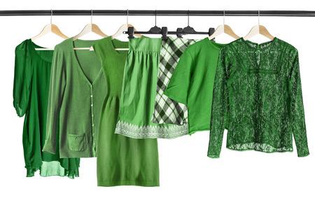 白で分離された服のラックに掛かっている緑服のグループ
