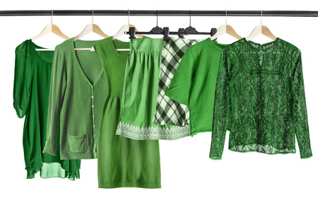 Group of green clothes hanging on clothes rack isolated over white