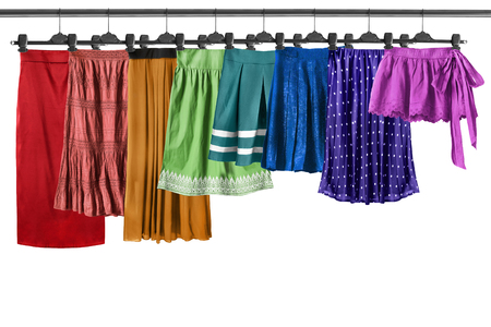 Set of colorful skirts on clothes racks isolated over white