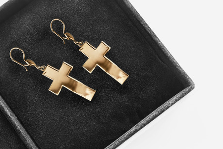 jewel box: Golden crosses earrings in black jewel box as a background Stock Photo