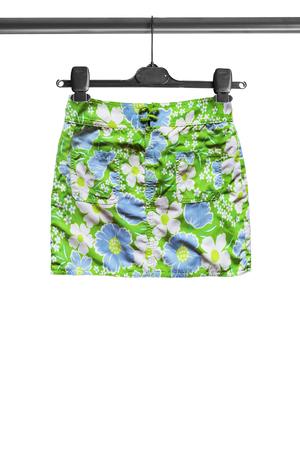 mini falda: mini falda verde en el estante de la ropa aislado m�s de blanco
