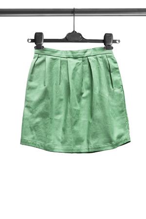 mini skirt: Green mini skirt on clothes rack isolated over white