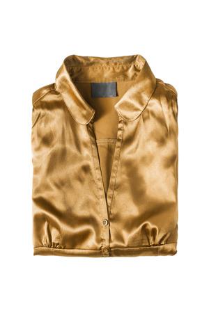 Golden satin blouse folded on white background