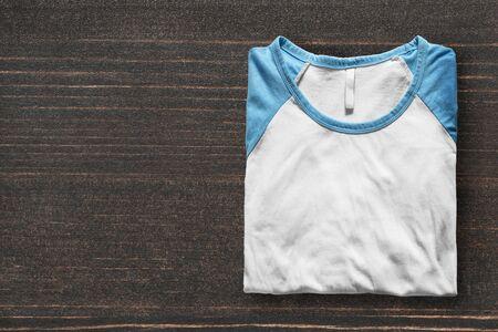 sports clothing: Folded sport shirt on dark wooden background