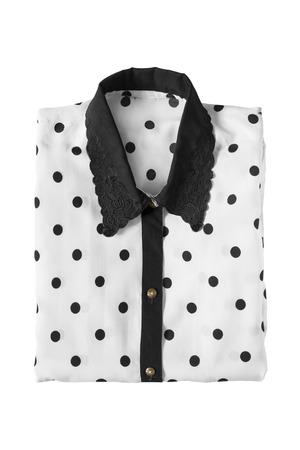 Black and white silk blouse folded on white background
