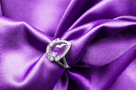draped: Silver amethyst ring on purple draped satin as a background