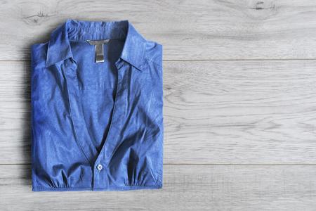 Blue blouse folded on white wooden background