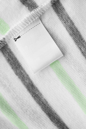 docket: Blank clothes label on striped cloth as a background
