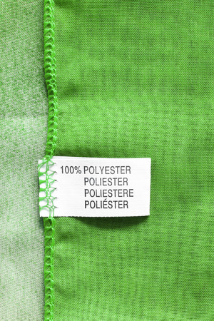 docket: Fabric composition label on green cloth as a background
