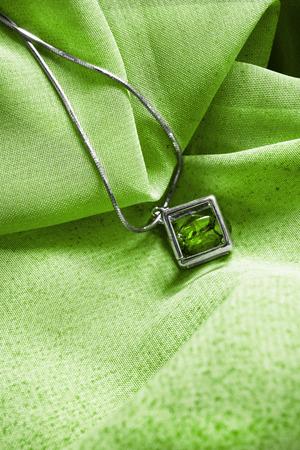 背景として緑の布でチェーンのエメラルド ペンダント